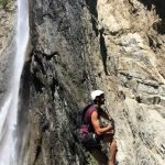 Client climbing alongside a waterfall